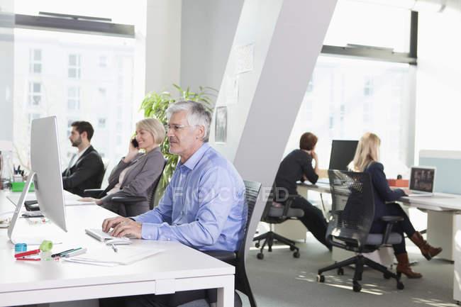 Бизнес-люди, работающие с компьютерами в современном офисе — стоковое фото