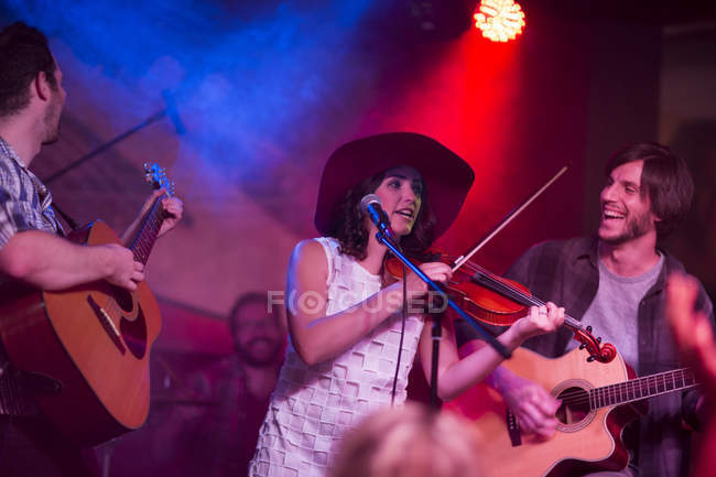 Folk band with violin, acoustic guitars and a drummer on a stage — Stock Photo