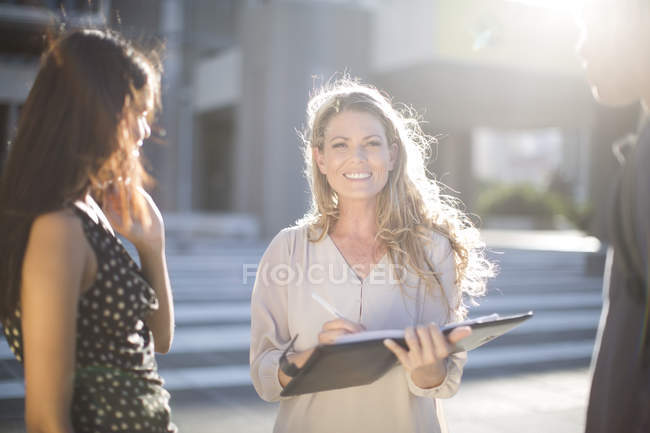 Two women and man standing  with folder in city — Stock Photo