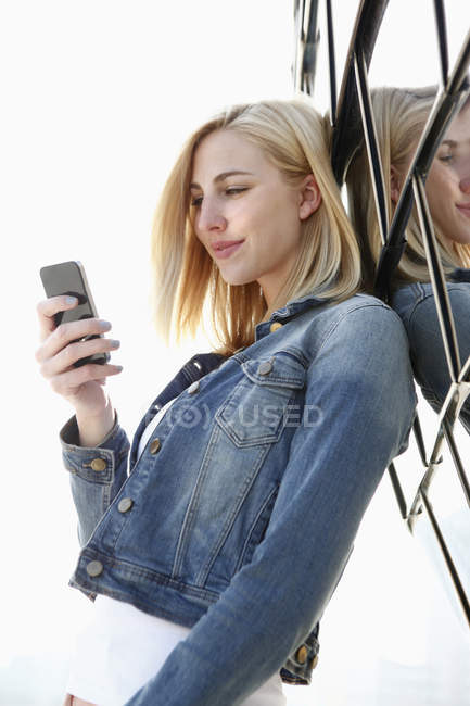 Sorridente donna bionda guardando il suo smartphone — Foto stock
