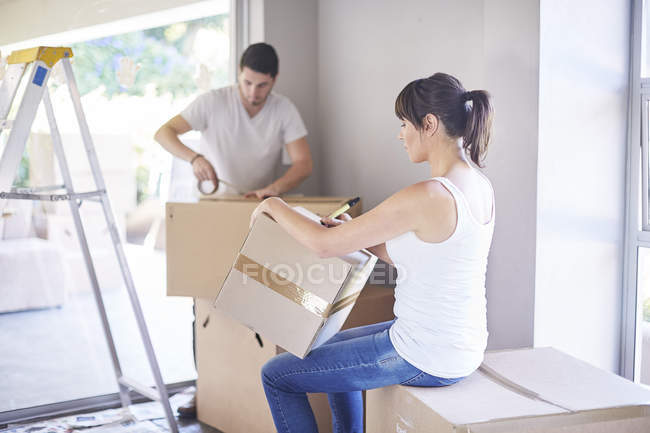 Couple se déplaçant dans la maison, la femme et l'homme d'écriture sur les boîtes — Photo de stock