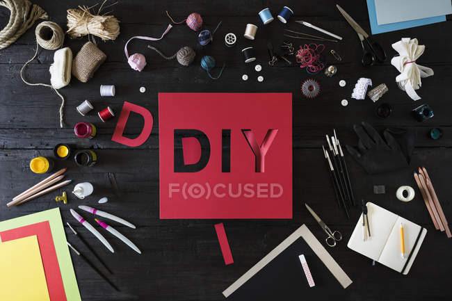 Craft materials, tools and red cardboard with the word DIY on black wood — Stock Photo