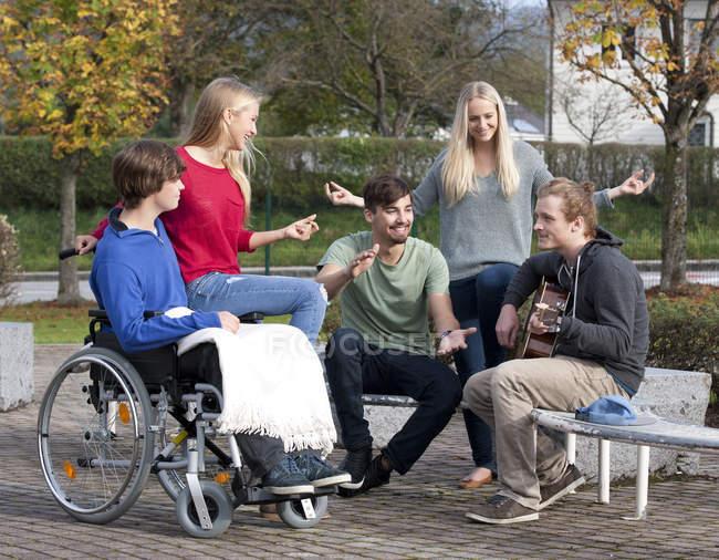 Четыре молодые люди прослушивания гитарист — стоковое фото