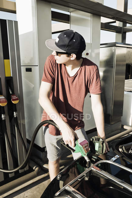 Adolescente à la station d'essence refuellng voiture décapotable — Photo de stock
