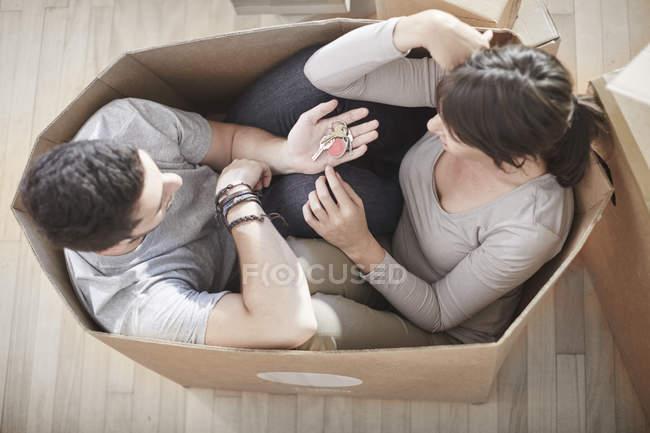 Casal casa em movimento sentado em uma caixa e segurando a chave — Fotografia de Stock