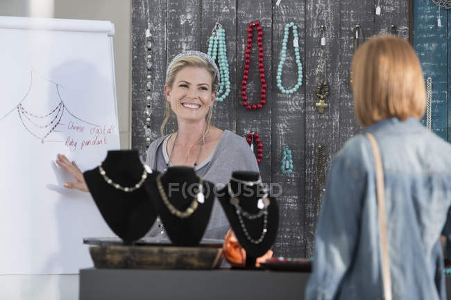 Woman showing a necklace design to a customer — Stock Photo