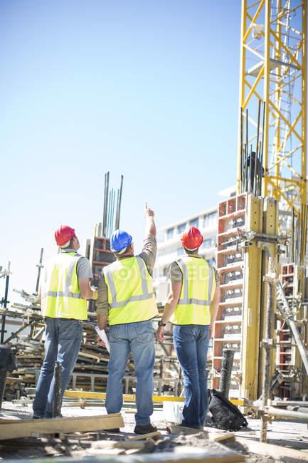 Три строителя на строительной площадке — стоковое фото