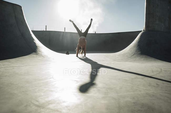 Girl doing a cartwheel in skatepark — Stock Photo