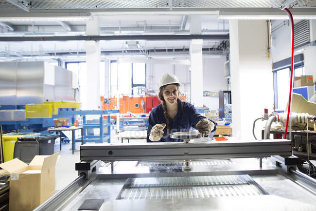 Smiling technician in factory hall adjusting plate — Stock Photo