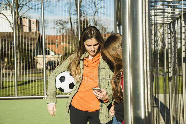 Girls on sports ground with cell phone — Stock Photo