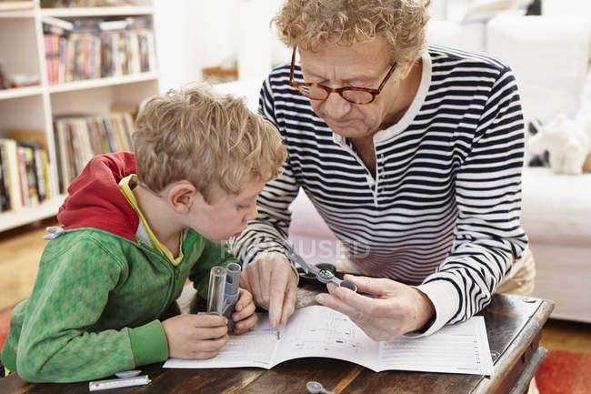 Abuelo y nieto montaje estación de juguete - foto de stock
