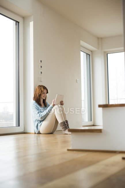 Молода жінка, сидячи на підлозі, використовуючи цифровий планшетний — стокове фото