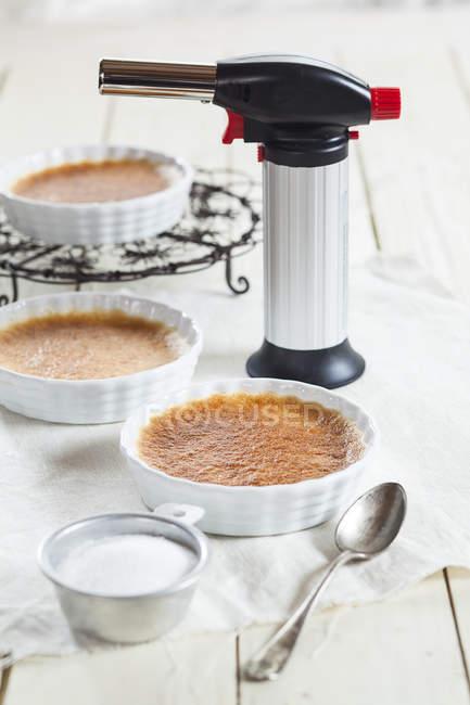 Крем-брюле в маленькой кухни до карамелизация — стоковое фото