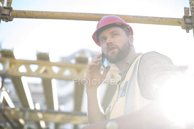 Працівник будівництва на мобільний телефон на будмайданчик — стокове фото