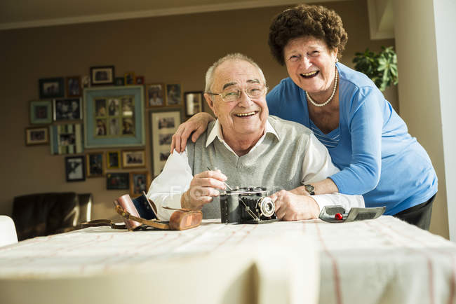 Happy senior couple with old camera at home — Stock Photo