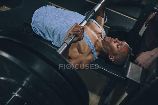 Young man exercising bench press in gym — Stock Photo