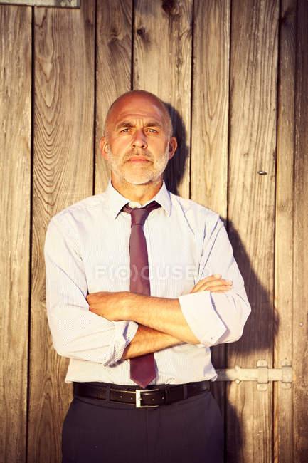 Ritratto di uomo con le braccia incrociate che indossa camicia e cravatta davanti alla parete di legno — Foto stock