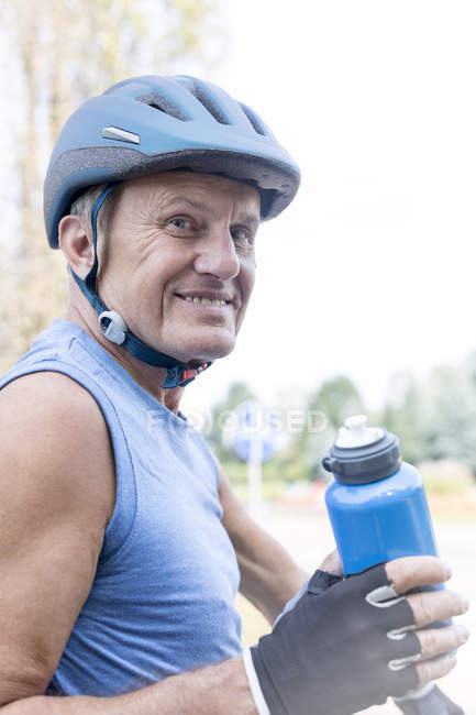 Portrait of senior man with cycling helmet and drinking bottle — Stock Photo