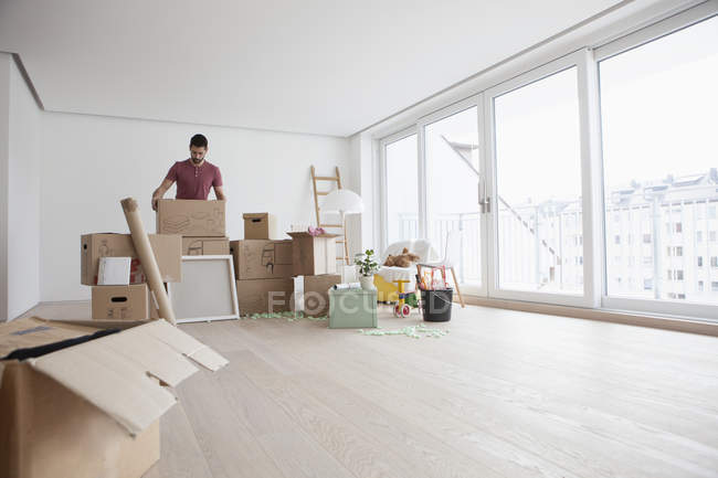 Young man in new flat unpacking cardboard boxes — Stock Photo