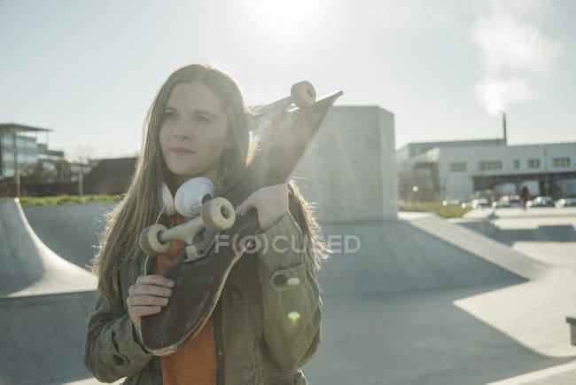 Mädchen im Skatepark hält skateboard — Stockfoto