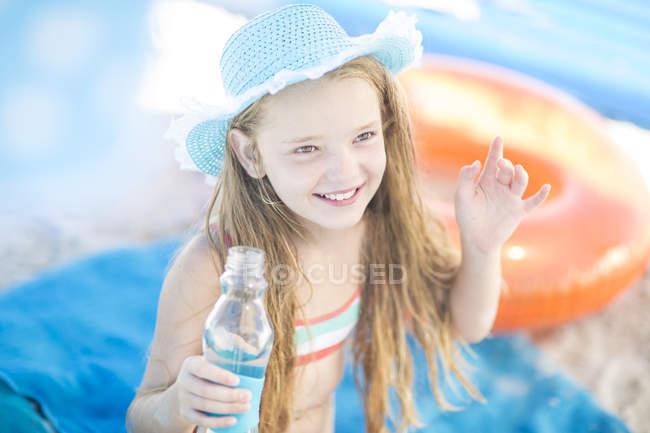 Улыбающаяся девушка на пляже держит бутылку воды — стоковое фото