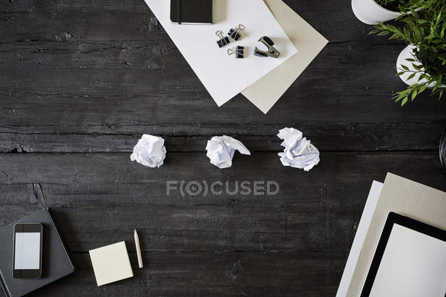Blank sheets of paper, pencil, smartphone and crumbled papers on black wood — Stock Photo