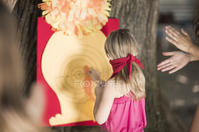 Girls in garden playing pin the tail on donkey — Stock Photo