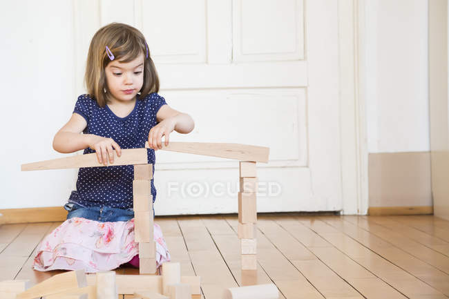 Little girl crouching on floor playing with wooden building bricks — Stock Photo