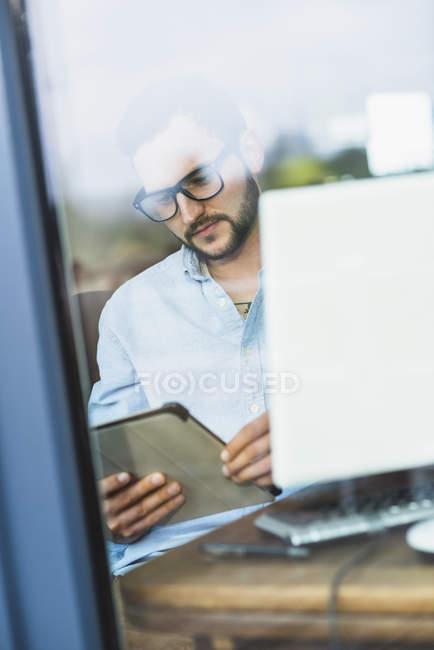 Junger Mann hinter Fensterscheibe blickt auf digitales Tablet — Stockfoto