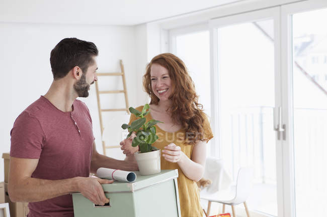 Young couple in new flat with cardboard boxes, unpacking boxes — Stock Photo