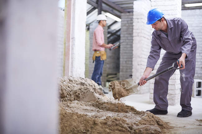 Construction worker mixing concrete with shovel with colleague on background — Stock Photo