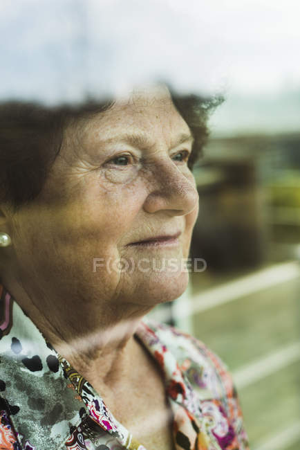 Portrait of senior woman looking through window — Stock Photo