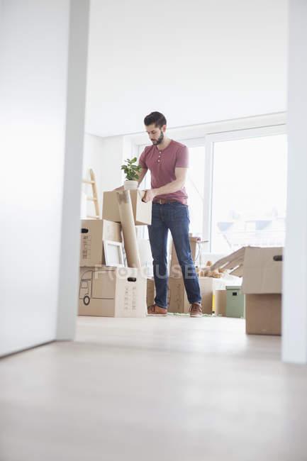 Hombre joven en cajas de cartón Desempaque planas nueva - foto de stock