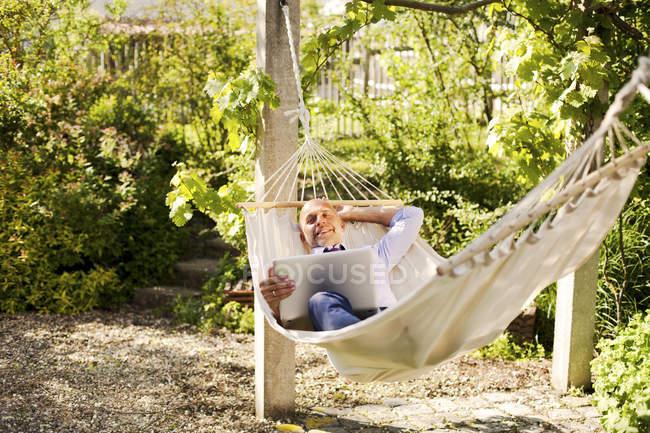 Бизнесмен с ноутбуком лежит в гамаке в саду — стоковое фото