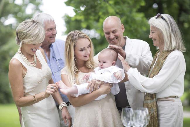Family gathering around baby outdoors — Stock Photo
