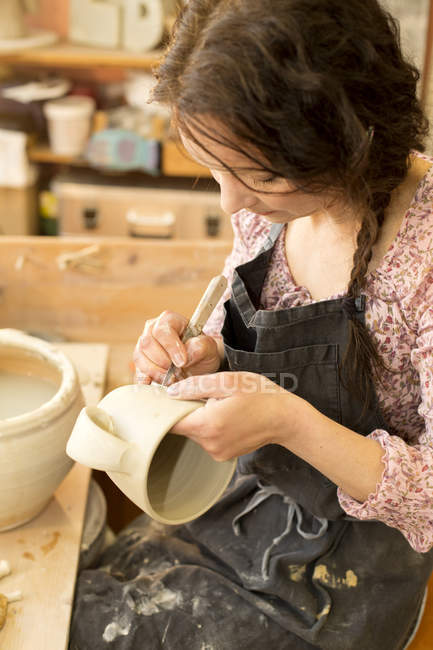 Potter in workshop working on earthenware jug — Stock Photo
