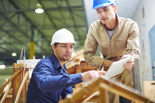 Trabalhador da construção civil e foreman discutindo as vigas do telhado — Fotografia de Stock