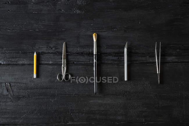 Reihe verschiedener Werkzeuge auf schwarzem Holz — Stockfoto