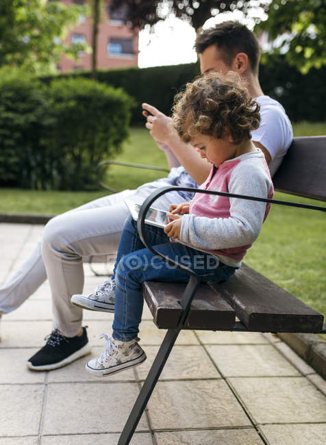 Young man and little girl sitting side by side on a bench looking at smartphone and digital tablet — Stock Photo
