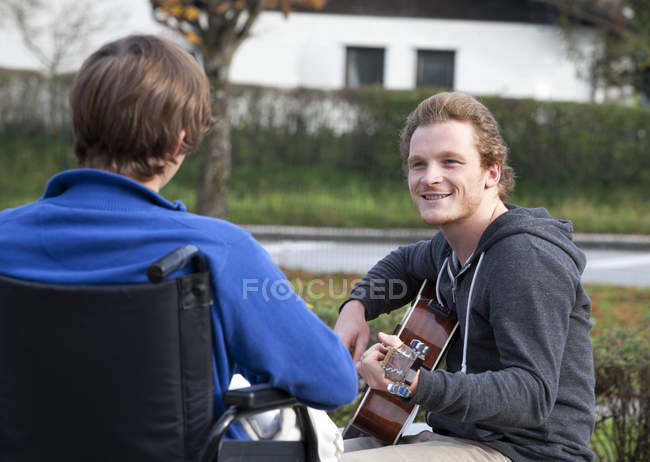 Молодой инвалидной коляске пользователь прослушивания гитарист — стоковое фото