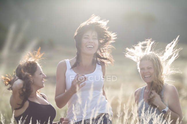 Female friends dancing and jumping in field — Stock Photo