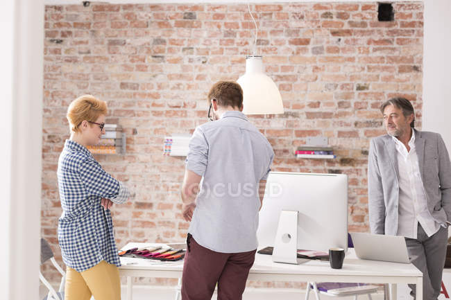 Three business people talking in modern office — Stock Photo