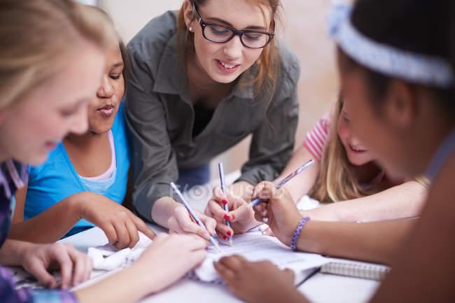 Enseignant et écolières écrivent sur papier ensemble — Photo de stock