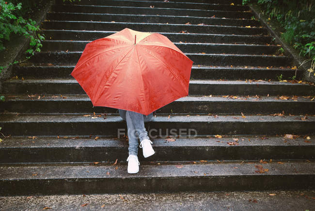 Teenage girl sitting on stairs hiding behind red umbrella — Stock Photo