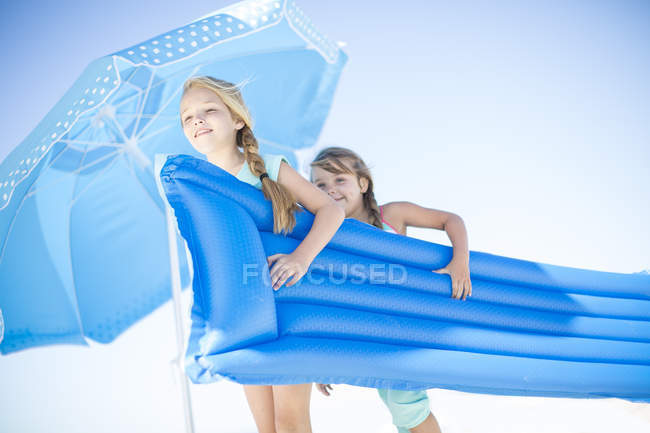 Two girls carrying a lilo together on beach — Stock Photo