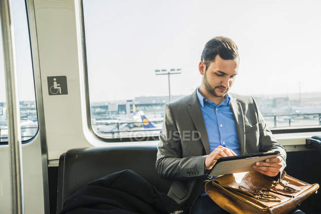 Germany, frankfurt, young businessman in bus at the airport — Stock Photo