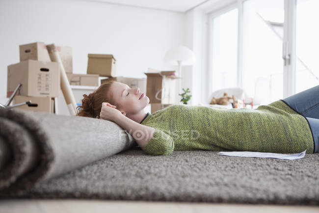 Young woman in new flat with cardboard boxes lying on carpet — Stock Photo