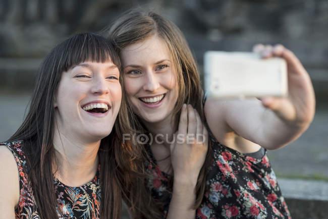 Zwei glückliche junge Frauen nehmen eine selfie — Stockfoto