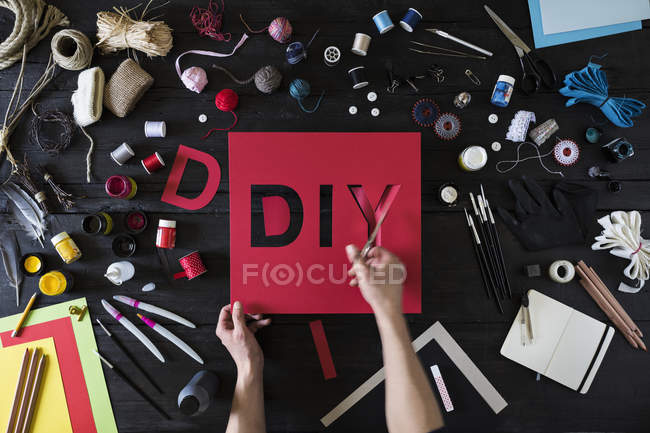 Man's hands cutting out the word DIY of red cardboard — Stock Photo
