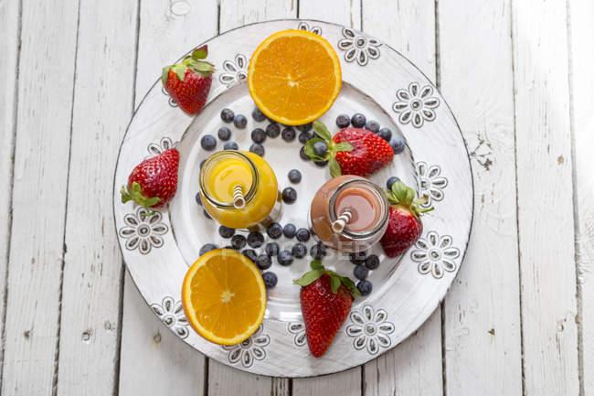 Smoothie orange et fraise en bouteilles de verre et fruits sur assiette — Photo de stock
